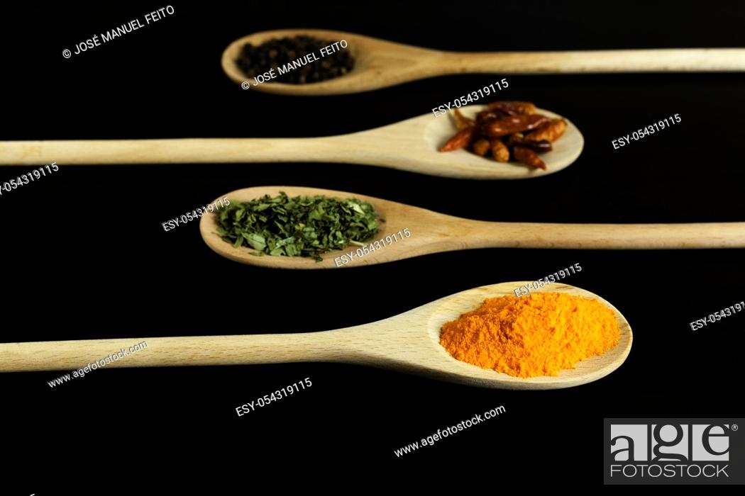 Stock Photo: four wooden spoons placed symmetrically with saffron, oregano, chillies and black pepper on dark background.