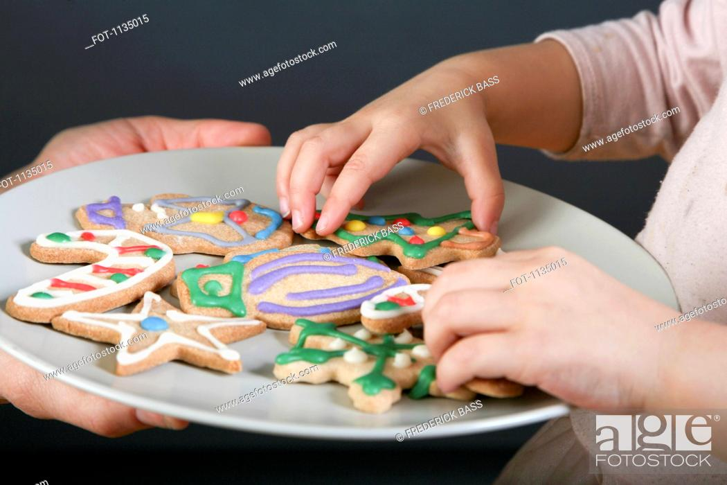 Stock Photo: A mother sharing a plate of Christmas cookies with her daughter, focus on hands.