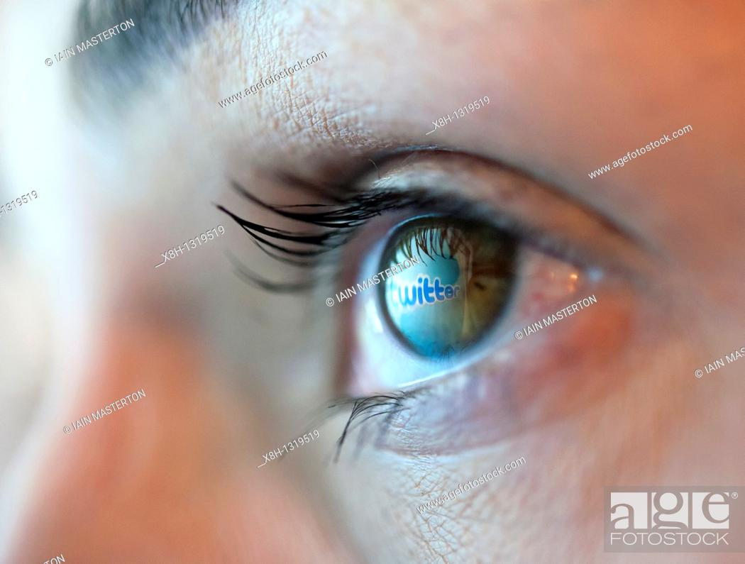 Stock Photo: Reflection from Twitter social messaging website reflected in woman's eye.