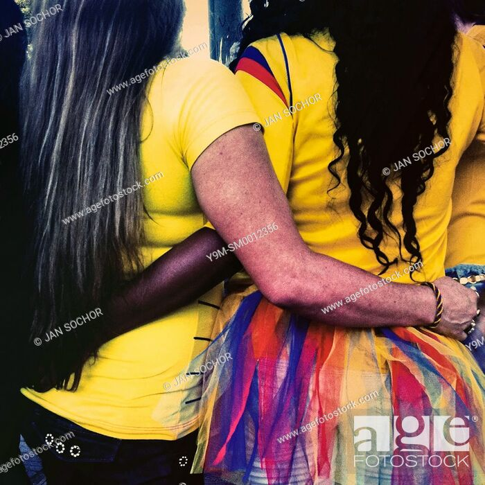 Stock Photo: Colombian girls, wearing the national football team t-shirt, embrace themselves while watching the football match between Colombia and Uruguay at the FIFA World.