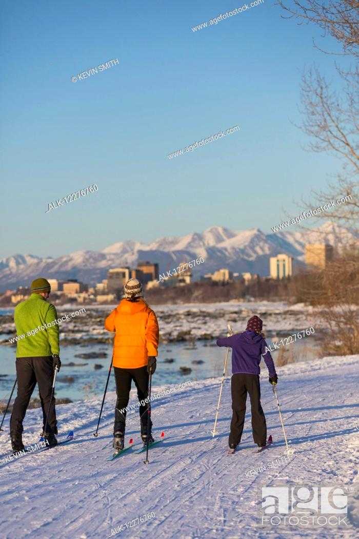 Stock Photo: People cross country skiing on the Tony Knowles Coastal Trail near Earthquake Park with Anchorage skyline in the background, Cook Inlet, Southcentral Alaska.