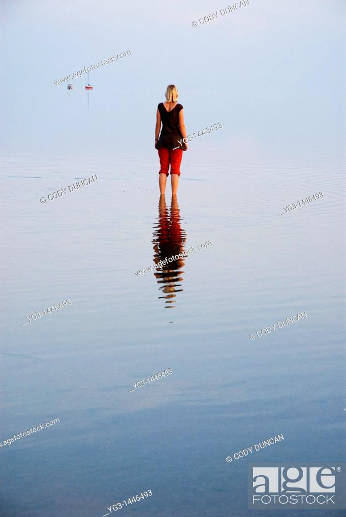 Stock Photo: Female standing in shallow water of German Wadden Sea, Juist, Lower Saxony, Germany.