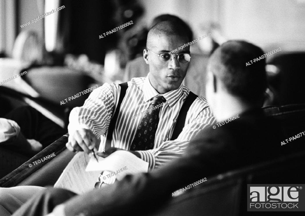 Stock Photo: Businessmen sitting, discussing document, b&w.