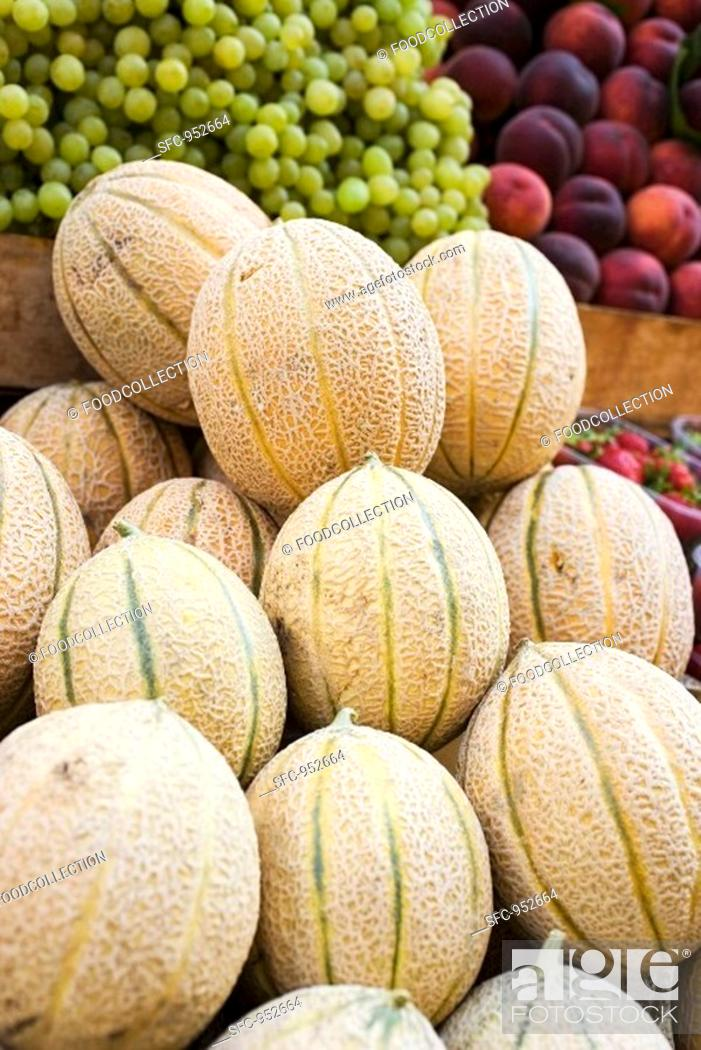 Stock Photo: Fresh melons, grapes and peaches at a market.