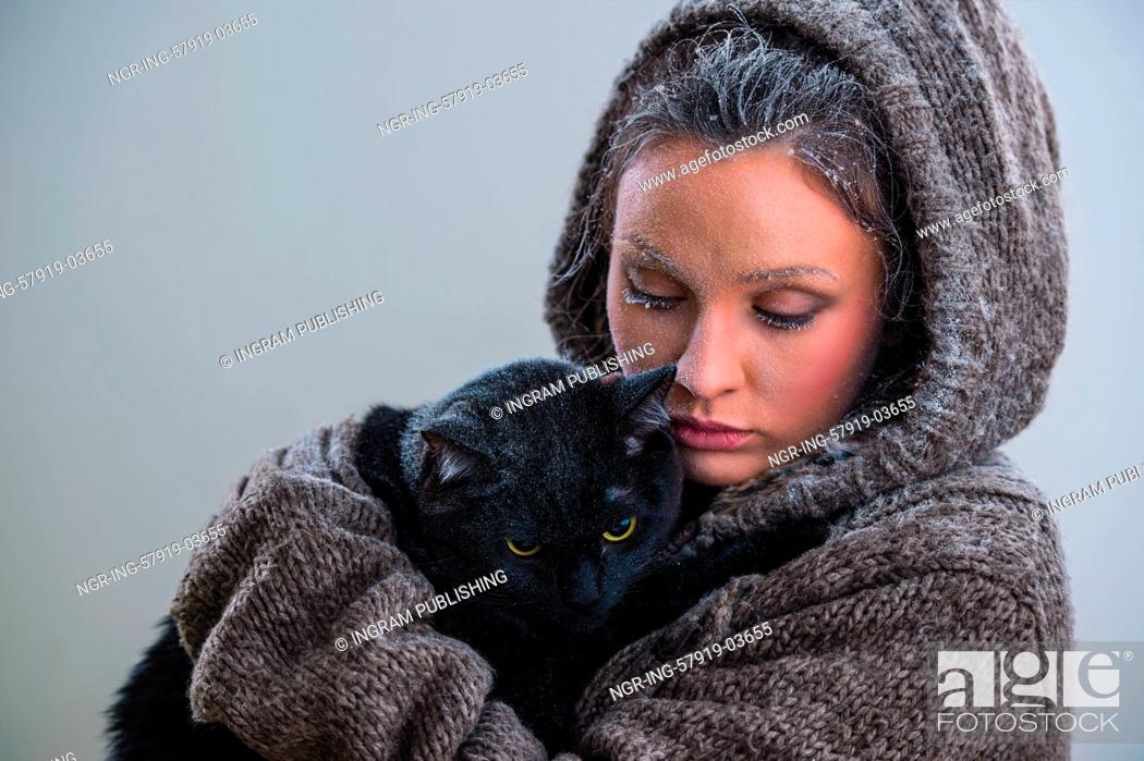Stock Photo: Winter portrait of young kind woman holding big black cat. Frost and snow on them.
