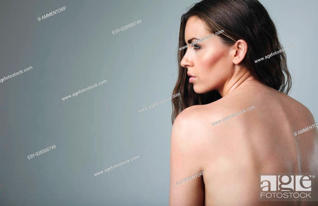 Stock Photo: Naked woman looking away at copy space on grey background. Topless caucasian female model.