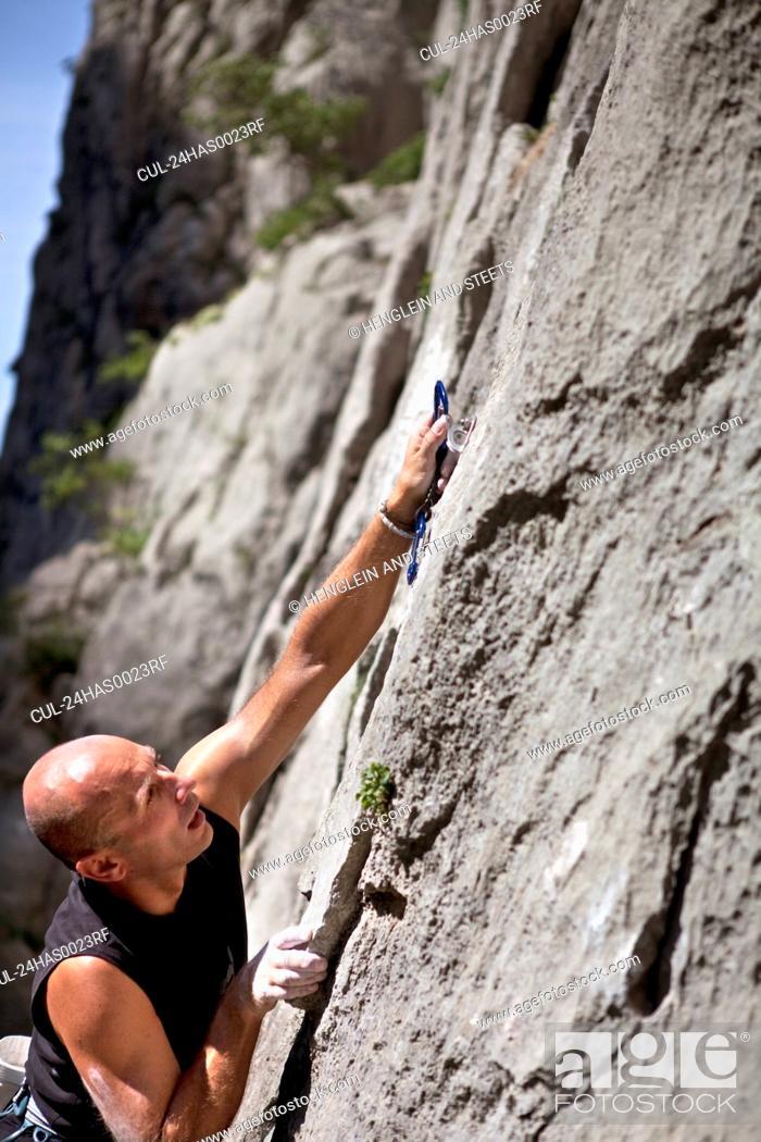 Stock Photo: Rock climber securing himself.