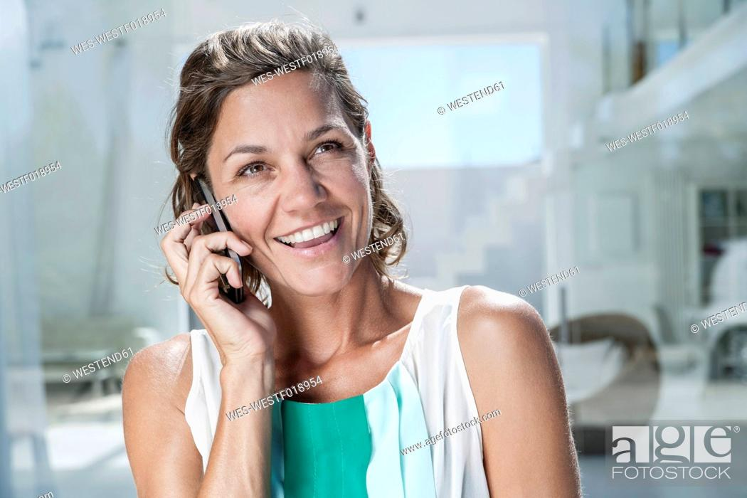 Stock Photo: Spain, Mid adult woman talking on cell phone.