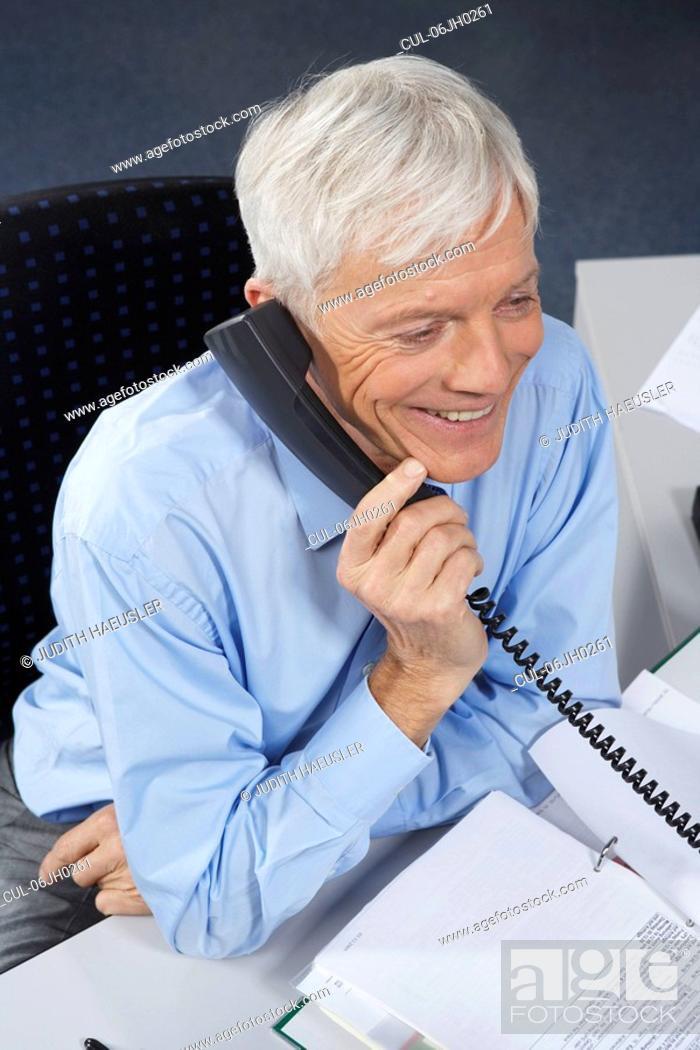 Stock Photo: Mature businessman at desk, on phone.