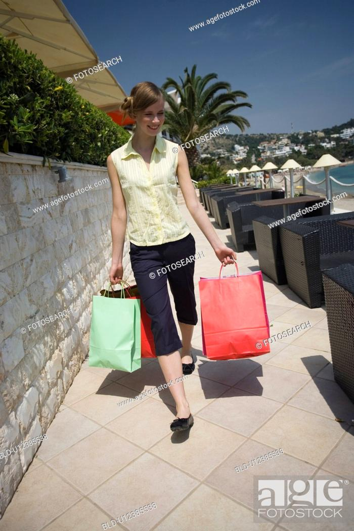 Stock Photo: Woman walking on promenade with shopping bags.
