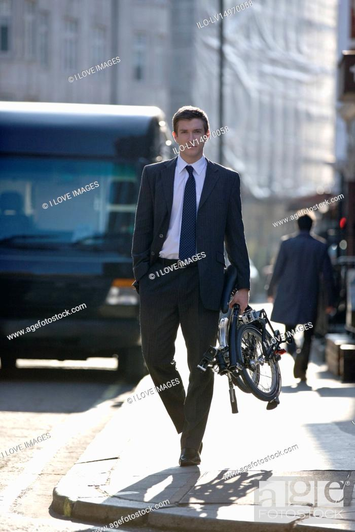 Stock Photo: A businessman carrying his folded bicycle along the street.