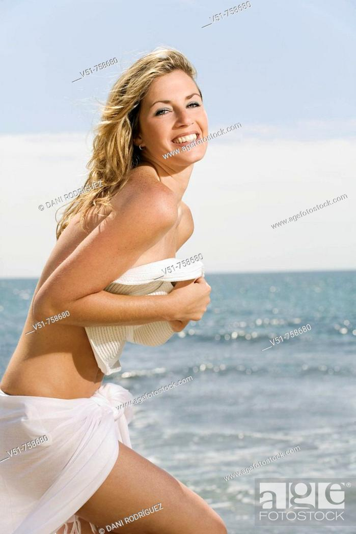 Stock Photo: Portrait of a blonde woman doing topless and hiding with a hat by the sea.