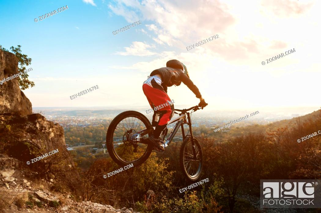 Photo de stock: a young rider at the wheel of his mountain bike jumps from high cliffs down against a backdrop of the cityscape at sunset.