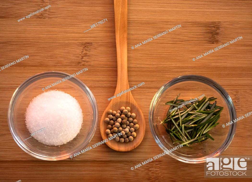 Imagen: Crystal bowl with common marine salt, a wooden spoon with white peppercorns and rosemary on a wooden table.