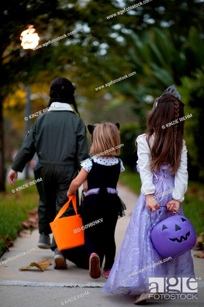 Stock Photo: Rear view of boy and sisters trick or treating walking on sidewalk.