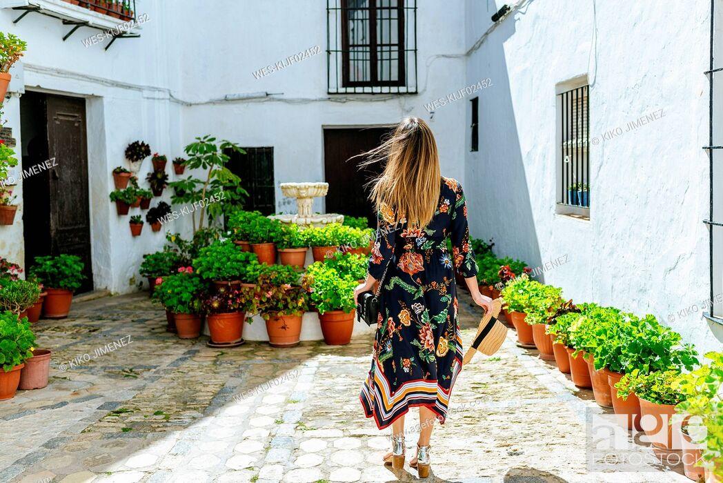 Photo de stock: Spain, Cadiz, Vejer de la Frontera, back view of fashionable woman standing at patio.