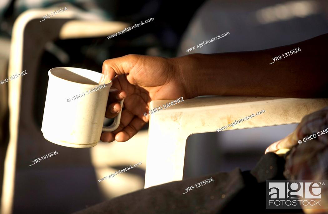 Stock Photo: A Central American migrant traveling across Mexico to work in the United States drinks a cup of coffee at the Catholic priest Alejandro Solalinde's shelter.