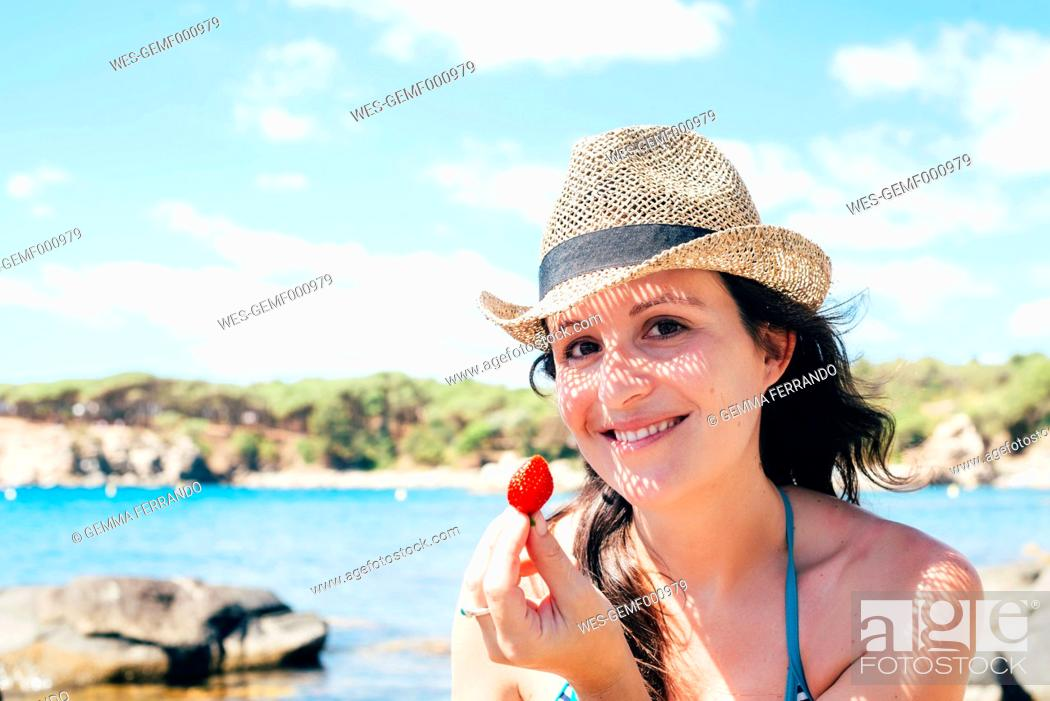 Stock Photo: Portrait of smiling woman wearing straw hat on the beach holding strawberry.