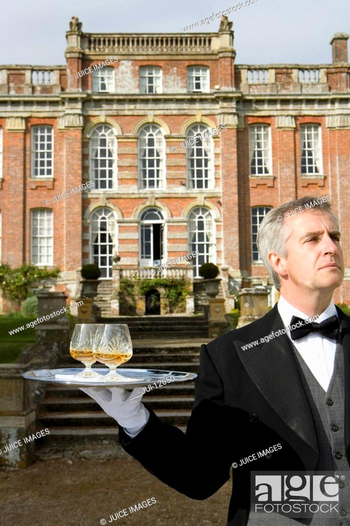 Stock Photo: Mature butler with drinks on tray by manor house, close-up.