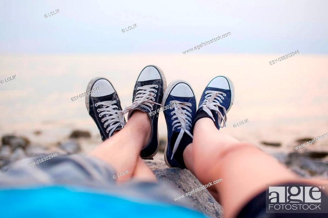 Stock Photo: The legs of a guy and a girl in the evening on the beach.