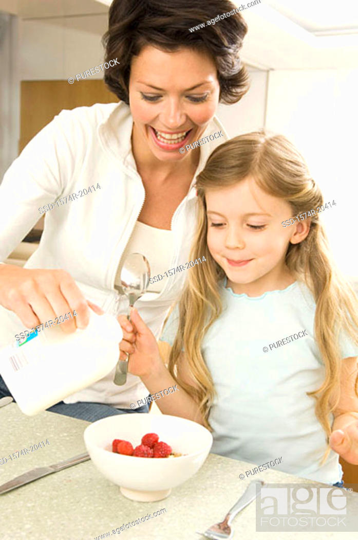 Stock Photo: Close-up of a young woman serving breakfast to her daughter.
