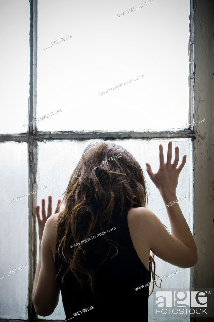 Stock Photo: Rear view of a young woman standing by the window.