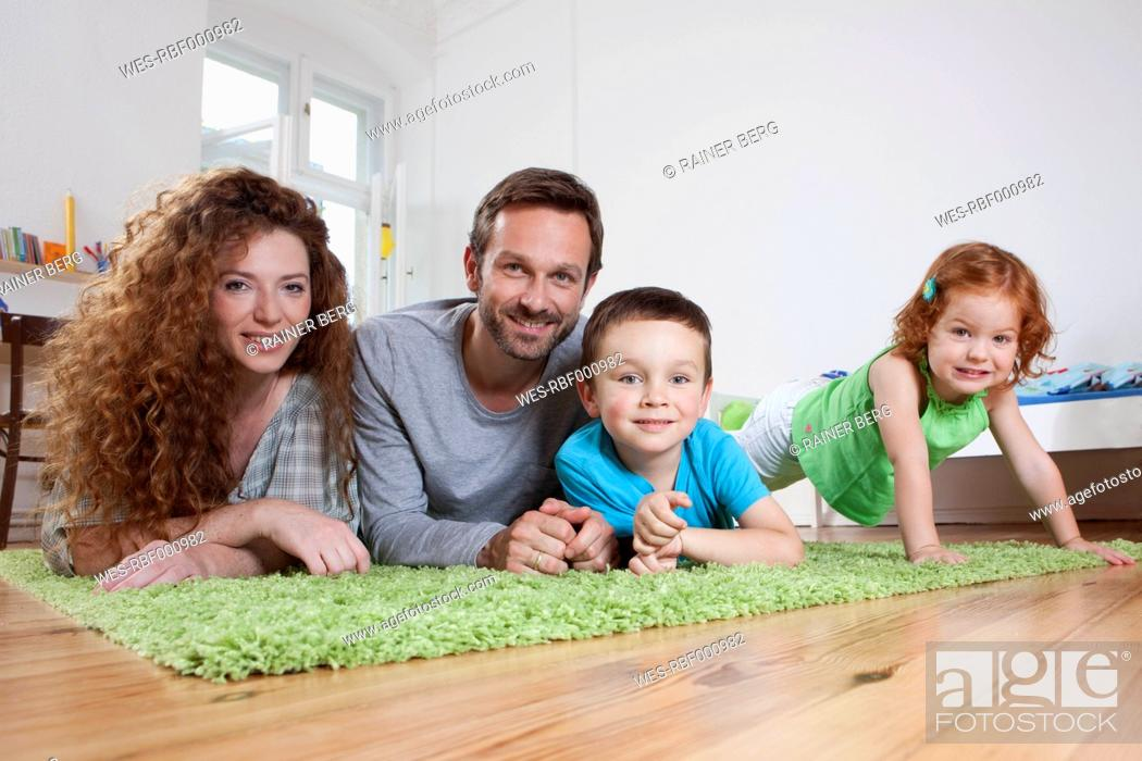 Stock Photo: Germany, Berlin, Family relaxing on floor, smiling, portrait.