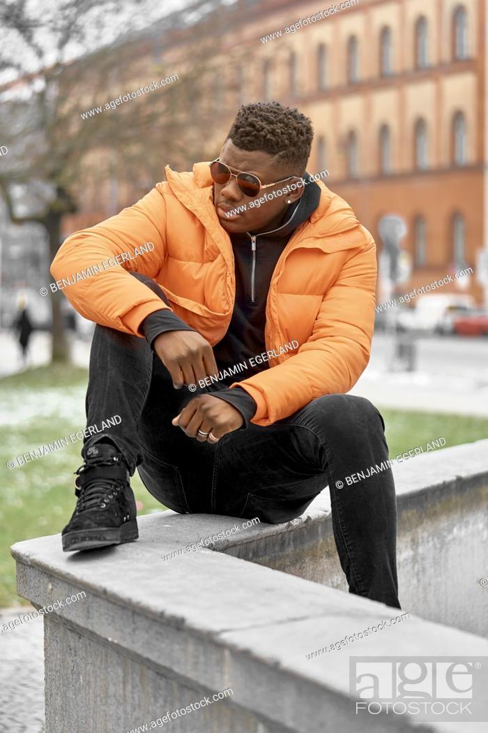 Stock Photo: stylish man wearing orange jacket in city, Munich, Germany.