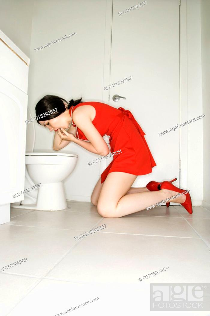 Stock Photo: Caucasian young adult woman kneeling in front of toilet trying to induce vomiting.
