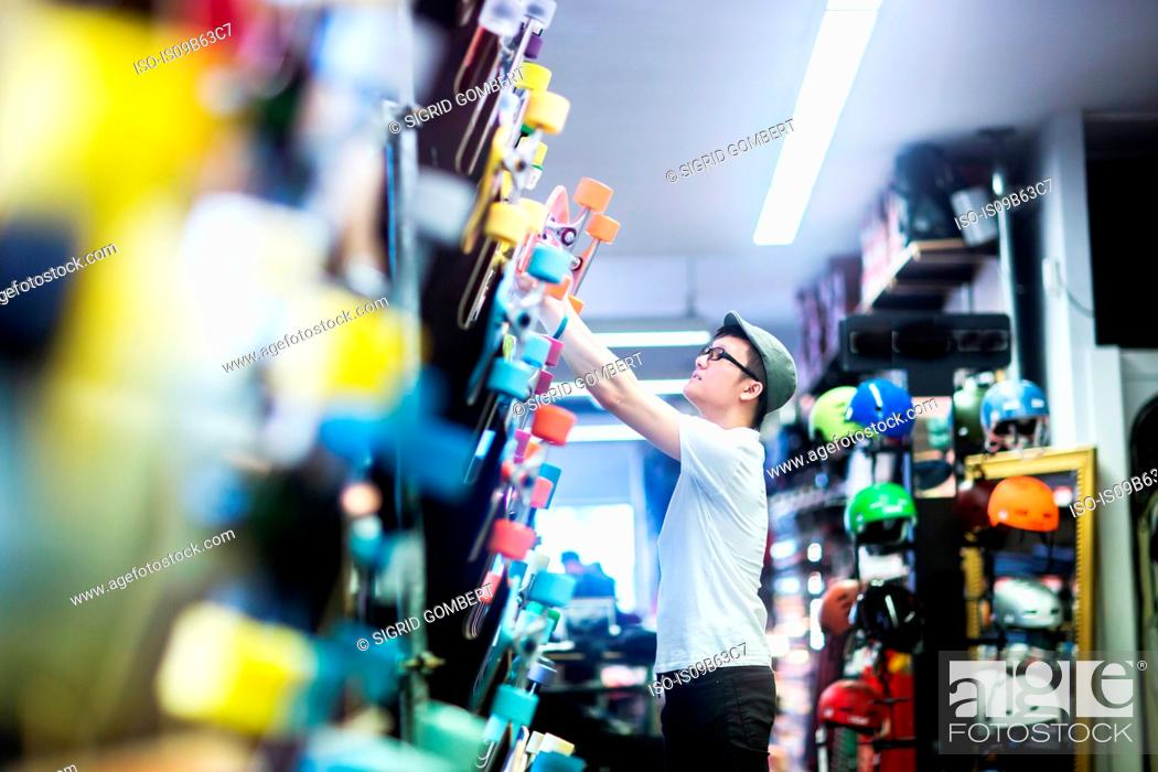 Stock Photo: Young male skateboarder removing skateboard from wall in skateboard shop.