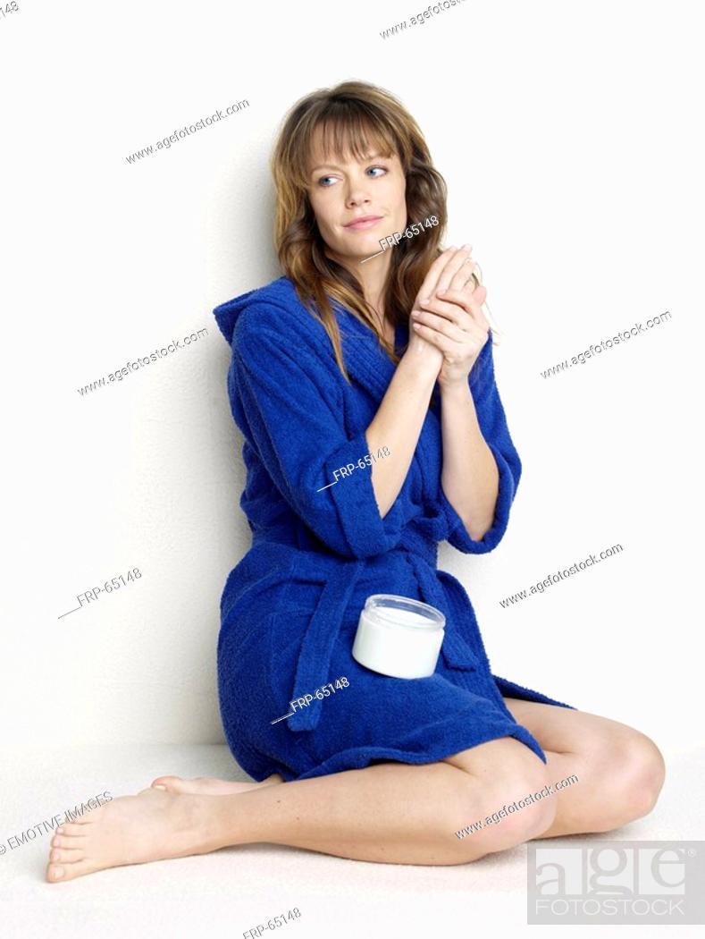 Stock Photo: Woman in blue bathrobe using body cream.