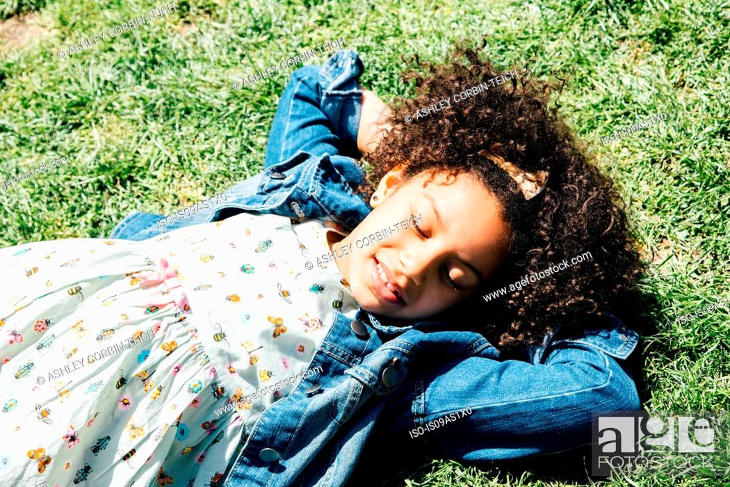 Stock Photo: High angle view of girl lying on back on grass, hands behind head, eyes closed.
