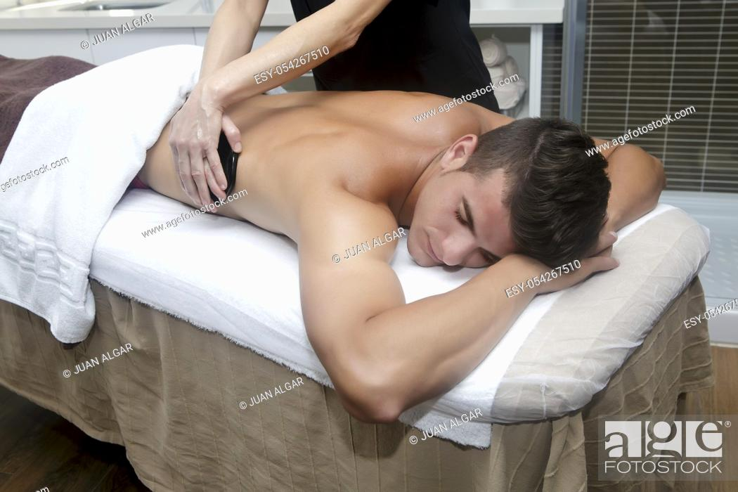 Stock Photo: Smiling brunet in spa getting massage with hot stones.