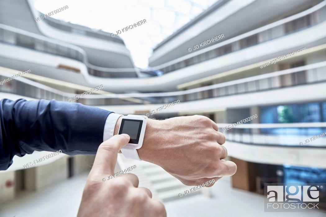 Stock Photo: Businessman touching smartwatch in office building.
