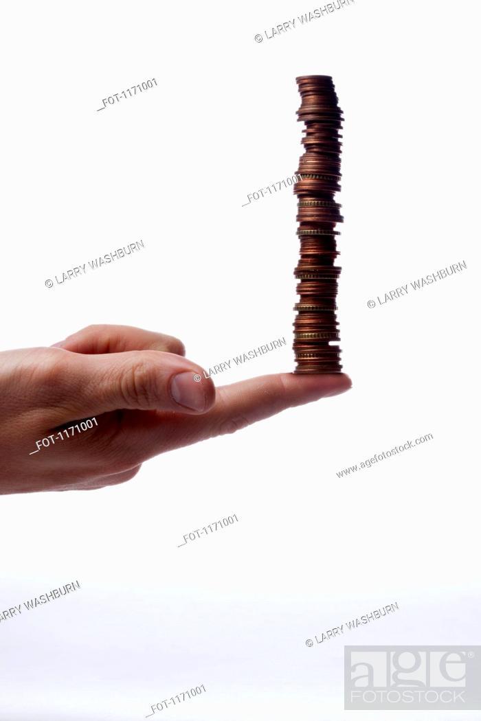 Stock Photo: A human finger balancing a stack of various Euro coins, close-up.