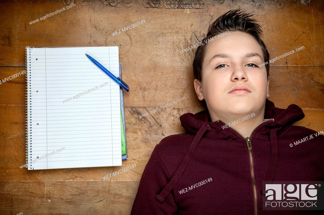 Stock Photo: Portrait of serious looking teenage boy lying beside a notebook on wooden floor.