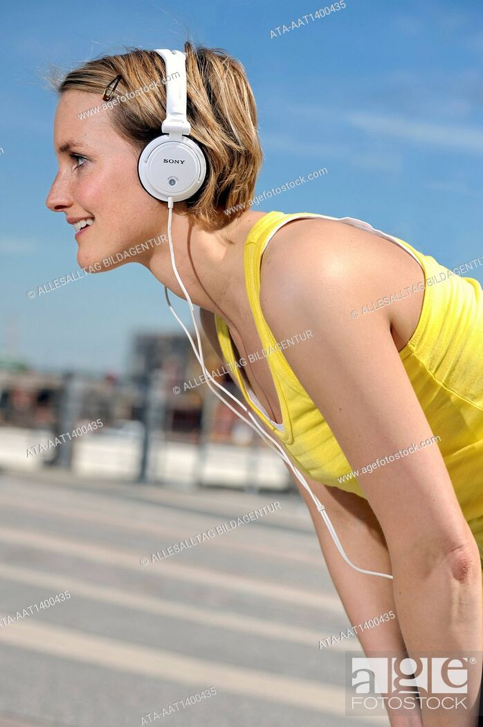 Stock Photo: Jogging woman with headphones takes a break.