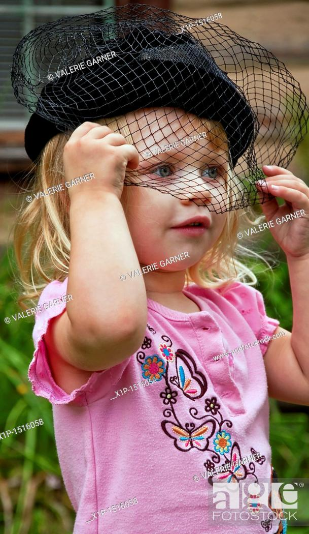 Imagen: This vertical image shows a cute 2 year old Caucasian girl, wearing a black vintage hat with a veil over her face.