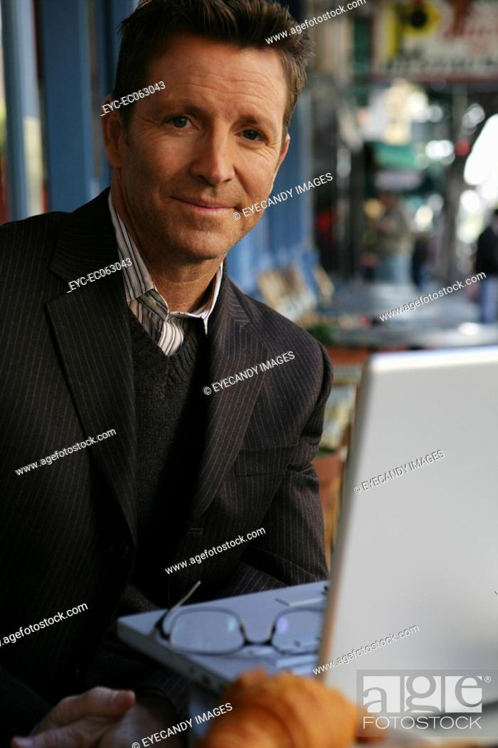 Stock Photo: Mature man working outside with a laptop.