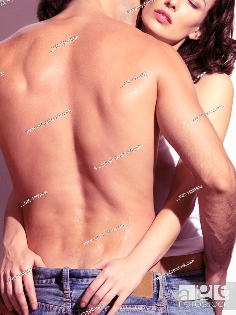 Stock Photo: Young woman embracing a man with bare torso, closeup of back, rear view.