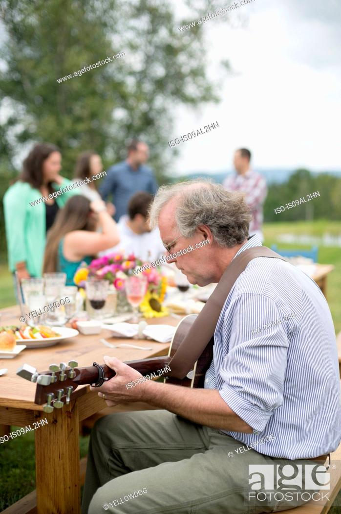 Imagen: Mature man playing guitar while friends and family talk together after meal, outdoors.
