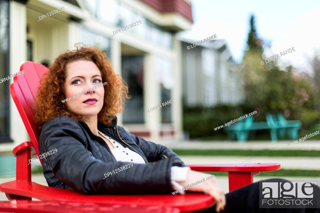 Stock Photo: Portrait of a woman with red, curly hair sitting outdoors in springtime; North Vancouver, British Columbia, Canada.