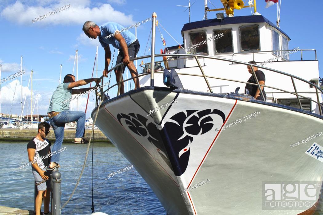 Imagen: fishermen getting on board, Castiglione della Pescaia, Tuscany, Italy.