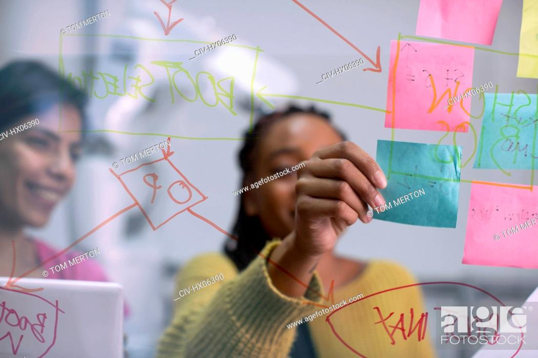 Stock Photo: Creative businesswomen using adhesive notes and flow chart, planning in office.