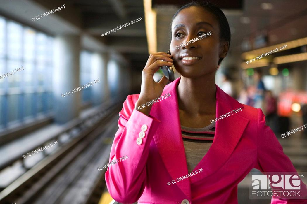 Stock Photo: Close-up of a young woman talking on a mobile phone at a subway station.