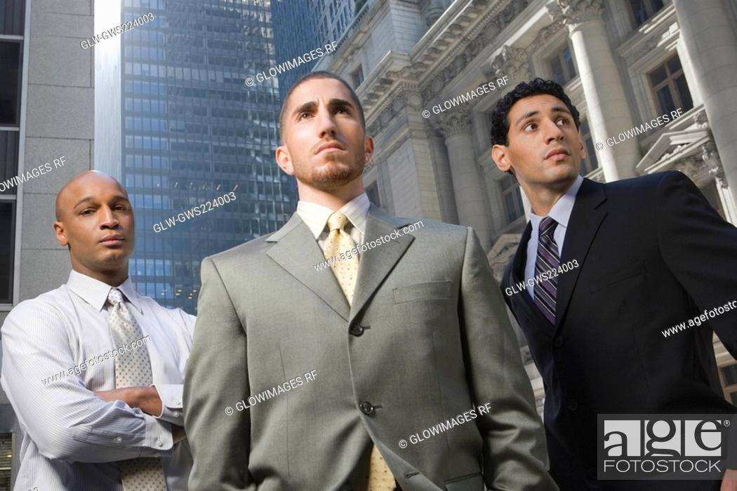 Stock Photo: Low angle view of three businessmen standing.