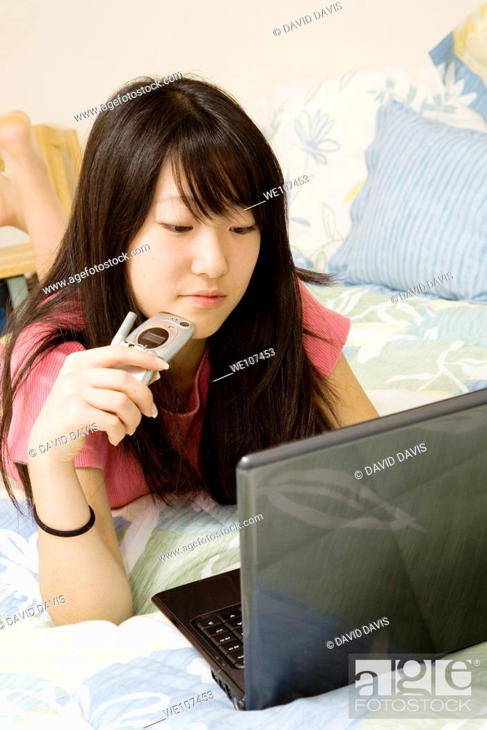 Stock Photo: Asian American teen working on laptop computer and talking on cell phone.