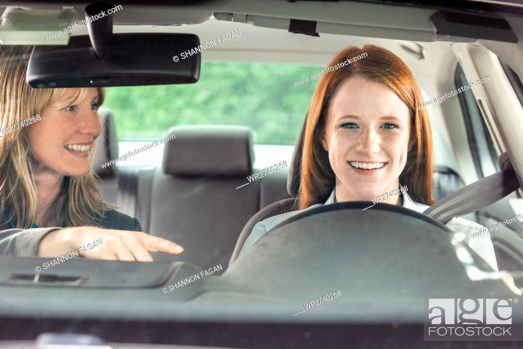 Stock Photo: Teenager in car with driving instructor.