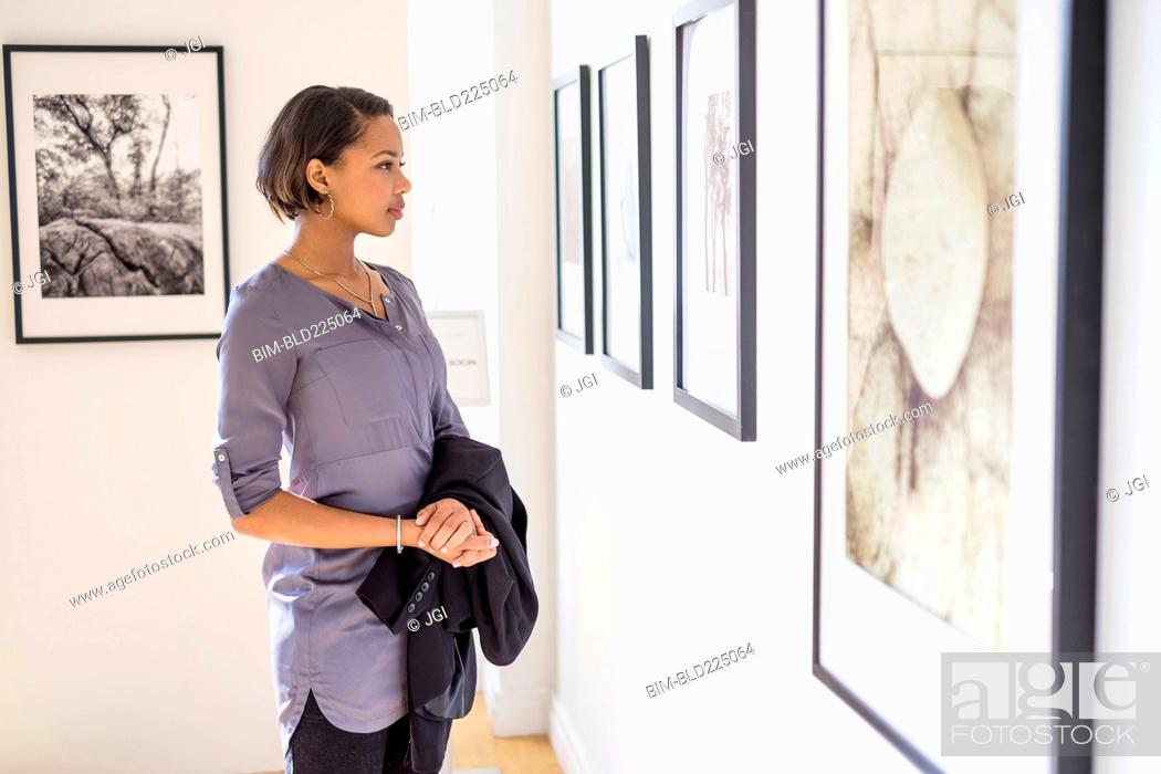 Imagen: Black woman admiring paintings in art gallery.