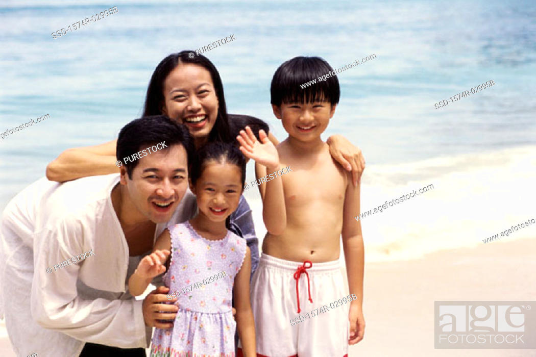 Stock Photo: Portrait of parents with their son and daughter on the beach.